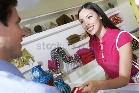Sales person : Clerk handing receipt to customer