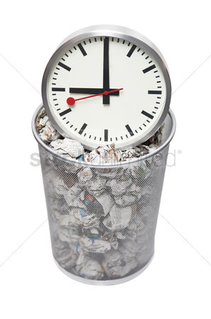Pile : Clock in wastebasket full of crumpled paper over white background