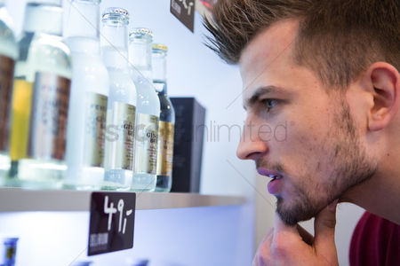 Czech republic : Close-up of man looking at beer bottles displayed on shelf in cafe