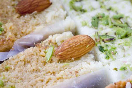 Almond : Close-up of milk cake and burfi garnished with almonds and pistachio