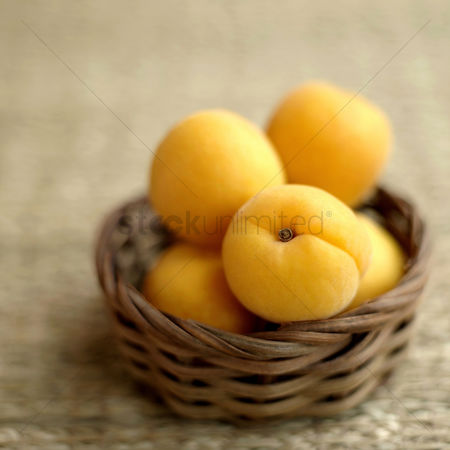 Food  beverage : Close up of some apricots in a woven container