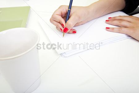 Furniture : Close up of womans hands writing on paper