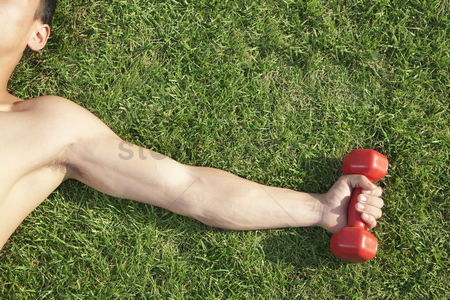 Dumbbell : Close up on arm and shoulder holding dumbbell in grass