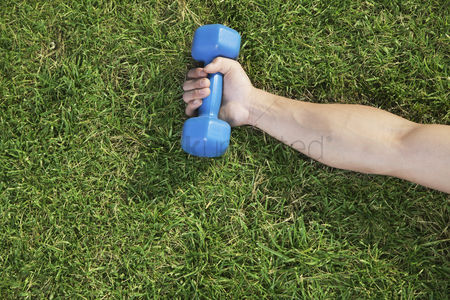 Dumbbell : Close up on hand holding blue dumbbell in grass