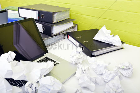 Technology background : Close-up view of crumpled paper over laptop on desk with empty chair and folders