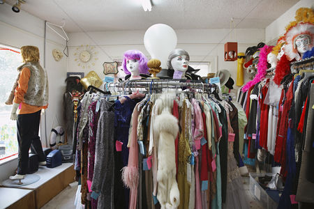 Vintage : Clothing and wigs in crowded second hand store