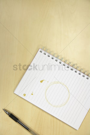 Notepad : Coffee ring on notebook on desk overhead view