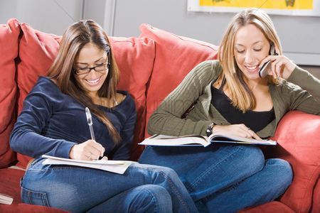 Cell phone : College students studying together on couch