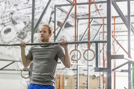 Muscle training : Confident man doing chin-ups in crossfit gym