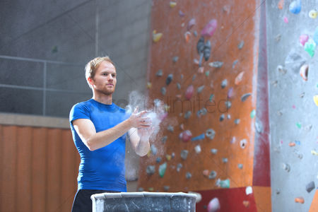 Rock wall : Confident man dusting powder by climbing wall in crossfit gym