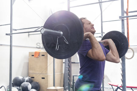 Muscle training : Confident man lifting barbell in crossfit gym
