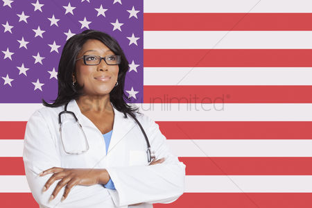 Respect : Confident mixed race female surgeon looking away over american flag