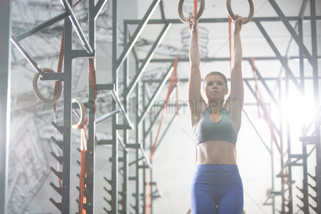 Three quarter length : Confident woman exercising with gymnastic rings in crossfit gym