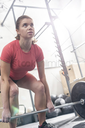 Muscle training : Confident woman lifting barbell in crossfit gym