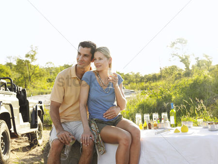 Wine bottle : Couple at picnic sitting and embracing