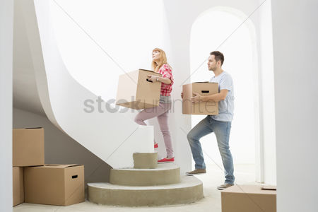 Relationships : Couple carrying cardboard boxes up stairs in new house