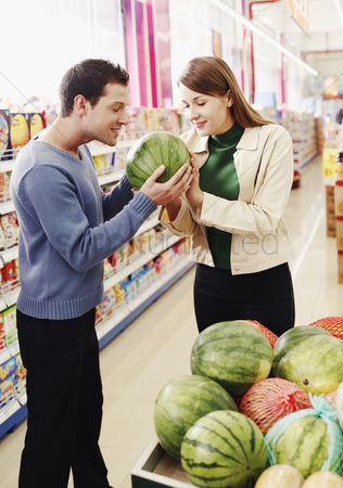 Having fun : Couple choosing water-melon in the supermarket
