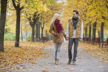 Two people : Couple holding hands while walking in park during autumn