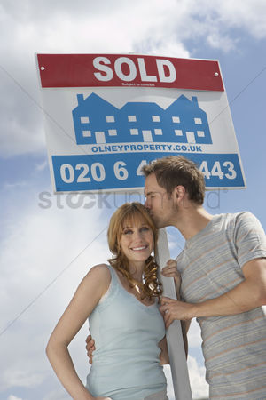 Kissing : Couple holding sold sign against sky man kissing woman
