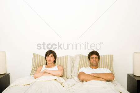 Interior : Couple in bed ignoring each other
