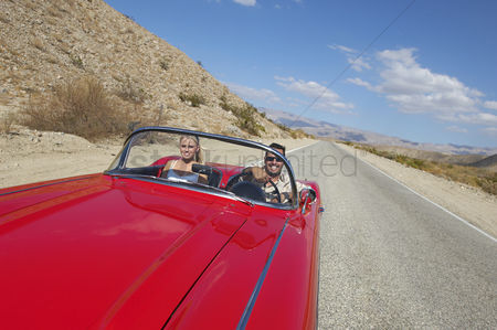 Transportation : Couple in classic car on desert road