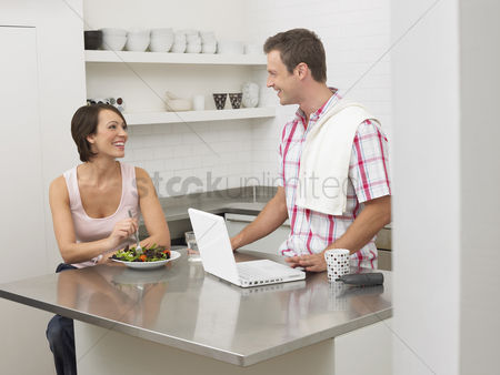 Productivity : Couple in kitchen woman eating man using laptop