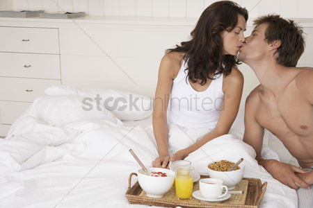 Relationships : Couple kissing and having breakfast in bed