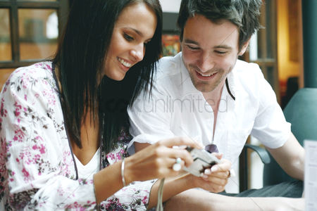 Smiling : Couple looking at digital camera