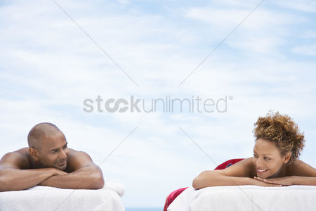 Indulgence : Couple lying on massage tables outside head and shoulders