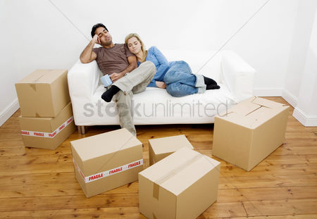 Lover : Couple napping on the couch with boxes on the floor