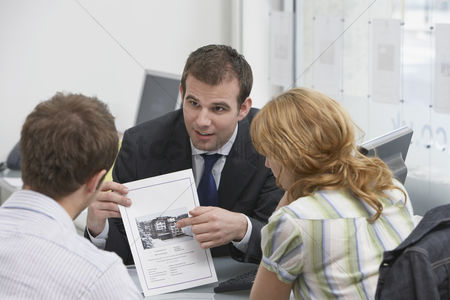 Business suit : Couple observing brochure with real estate agent in office