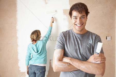 Paint brush : Couple painting interior wall using brush and roller