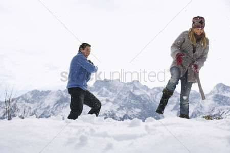 Fight : Couple playing in snow on hill low angle view