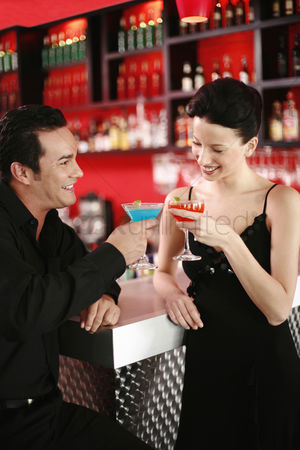 Celebrating : Couple proposing a toast while drinking in a bar