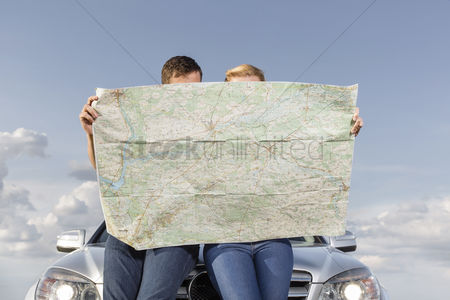 Transportation : Couple reading map while leaning on car hood during road trip