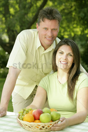 Green grapes : Couple sitting at the picnic table with a basket of fruits