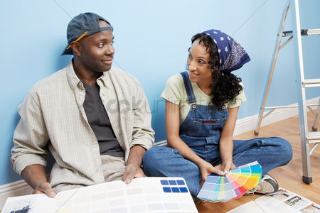Smiling : Couple sitting on floor of room looking at paint colour samples