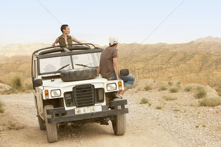 Land : Couple sitting on stationary four wheel drive vehicle in desert