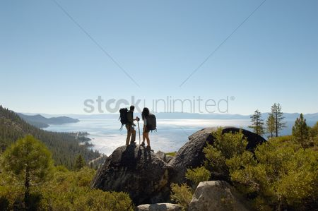 People : Couple standing on rock at coast