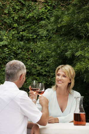 Toasting : Couple toasting with wine glasses sitting outdoors