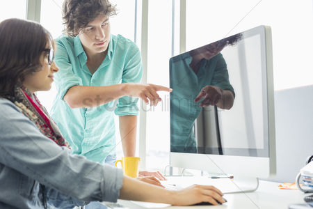 Two people : Creative businessman showing something to colleague on desktop computer in office