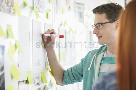 Two people : Creative businessman writing notes on paper in office