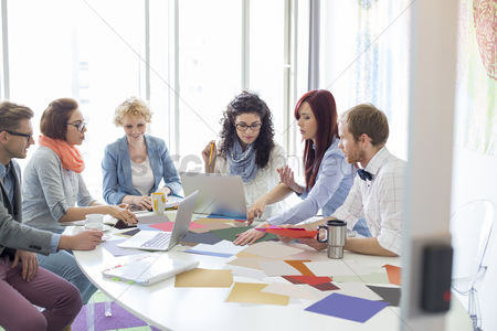 Creativity : Creative businesspeople analyzing photographs at conference table in office
