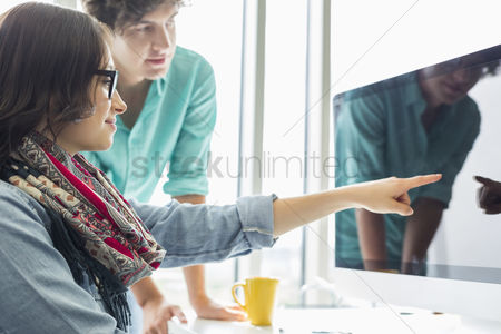 Two people : Creative businesswoman showing something to colleague on desktop computer in office