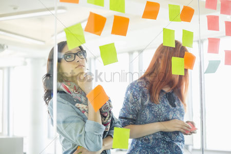 Two people : Creative businesswomen reading sticky notes on glass wall in office