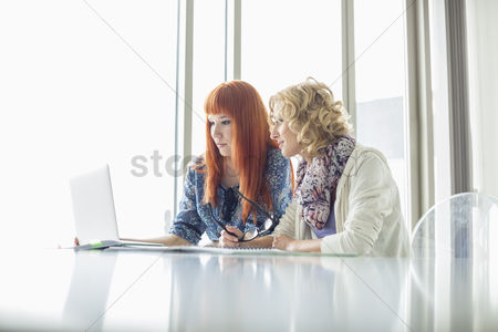Window : Creative businesswomen working on laptop together in office