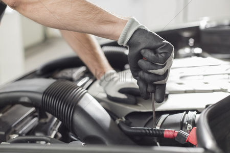 Car : Cropped image of automobile mechanic repairing car in automobile store