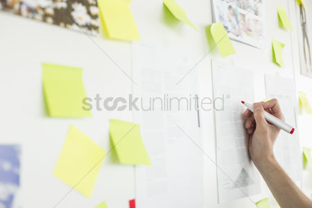 Women : Cropped image of businessman s hand writing on paper in office