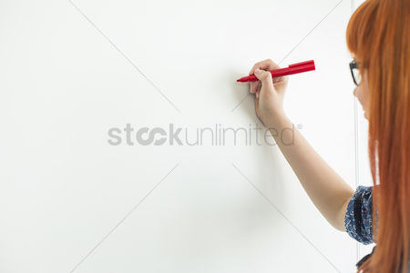 Creativity : Cropped image of businesswomen writing on whiteboard in creative office