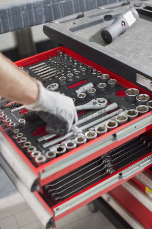 Variety : Cropped image of male mechanic taking tool from drawer in car workshop